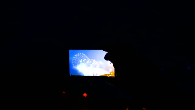 Man-shoots-fireworks-on-the-phone-and-watches-salute-through-the-smartphone-screen