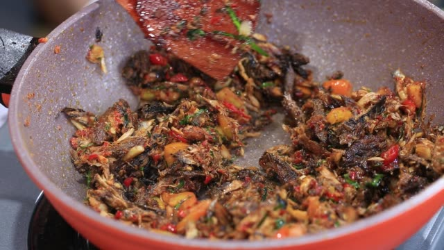 Chef-prepares-meats-with-sweet-chili-sauce-in-frying-pan-Bali-Indonesia-close-up