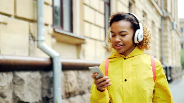 Feliz-chica-afroamericana-está-escuchando-música-con-auriculares-inalámbricos-y-utilizando-smartphone-caminando-al-aire-libre-disfrutando-de-la-canción-y-a-pie-Concepto-de-gadgets-y-Milenio-