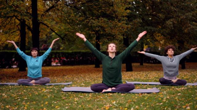 Spititual-jóvenes-están-meditando-sentado-en-posición-de-loto-sobre-esteras-de-la-yoga-en-el-parque-y-respirar-aire-fresco-relajante-después-de-la-práctica-al-aire-libre-Concepto-de-meditación-y-de-la-naturaleza-