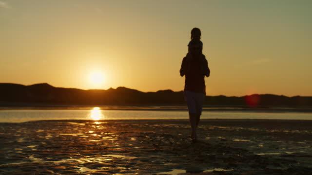 Silueta-del-padre-paseando-con-el-hijo-sobre-sus-hombros-en-la-playa