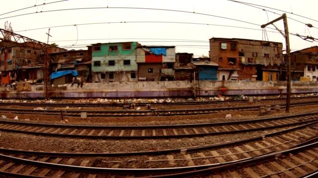 Nahverkehrszug-mit-Fahrgästen-fliegt-vor-der-Sicht-auf-Bahnlinien-und-den-Armenbezirk-Mumbai