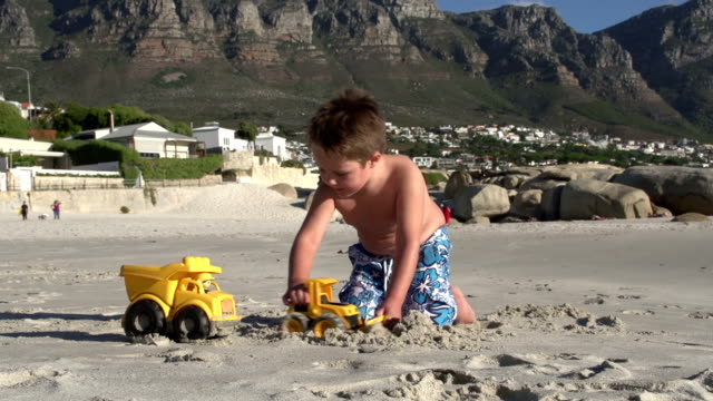 Young-boy-playing-with-toys-on-beach-Cape-Town-South-Africa