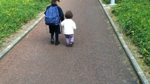 Joven-hermana-camina-con-su-hermana-mayores-a-escuela