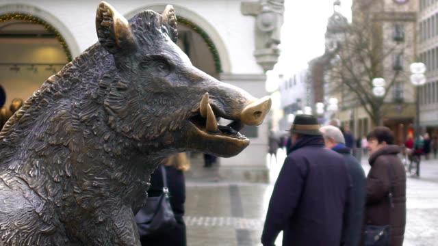 Bronze-statue-of-wild-boar-in-historical-city-center-tourists-walking-around