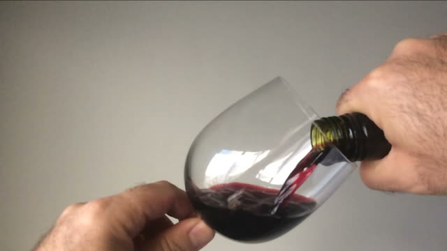 Slow-motion-of-a-man-pouring-red-wine-from-a-bottle-into-a-wine-glass