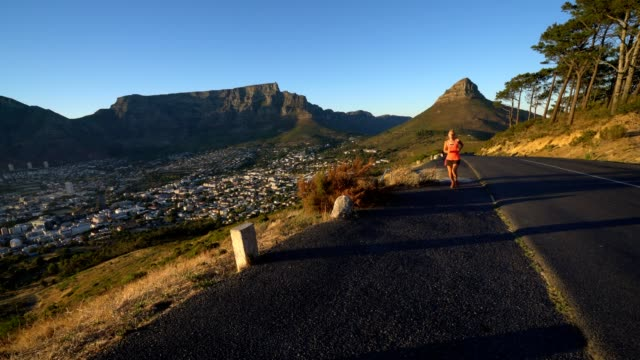 Young-woman-running-at-sunrise-Cape-Town-South-Africa