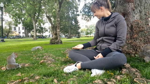 CLOSE-UP:-Joven-dando-alimento-a-las-ardillas-en-el-parque-Boston-Common-Estados-Unidos