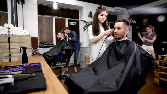 Two-friends-visiting-modern-barbershop-Handsome-hipsters-sitting-against-mirror-and-working-with-hairstylists-Smiling-man-and-woman-using-professional-equipment-for-making-stylish-haircuts