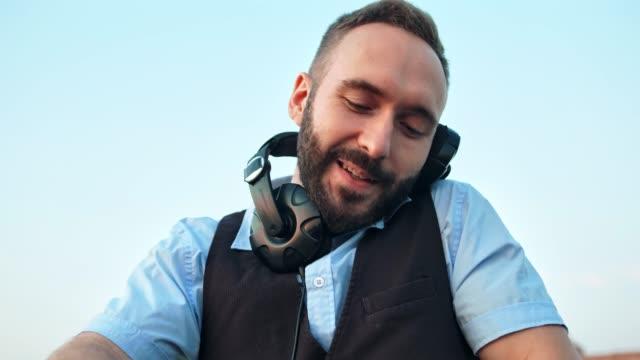Retrato-de-ángulo-bajo-entusiasta-DJ-hombre-feliz-en-auriculares-en-fiesta-de-discoteca-o-terraza-al-aire-libre