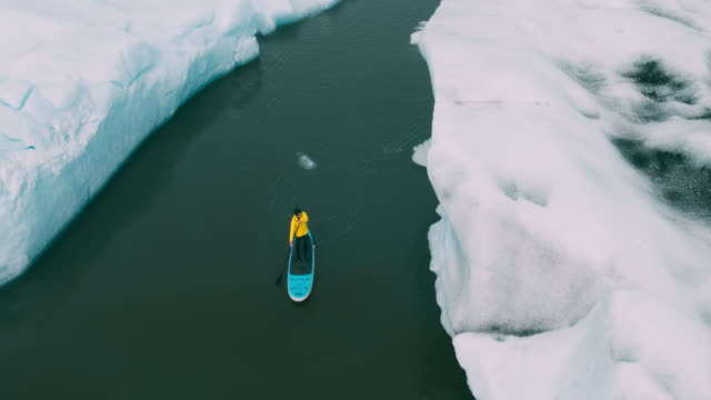 Joven-aventurero-infantil-stand-up-paddle-board-a-través-de-icebergs-en-el-lago-glaciar-en-Islandia