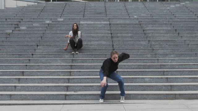 Niña-sentada-sobre-pasos-de-danzas-de-otra-chica-en-pasos