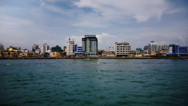 Drone-flying-low-above-the-ocean-water-towards-Colombo-city-coastline-Sri-Lanka-modern-buildings-on-the-shore-line