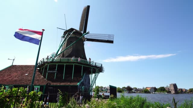Tourists-couple-taking-pictures-of-traditional-Windmills-at-the-Zaanse-Schans-near-Amsterdam-Holland