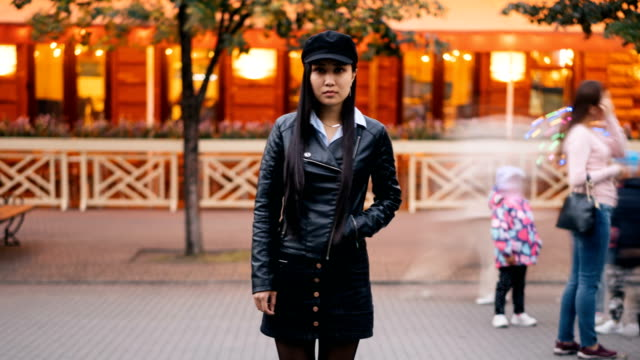 Zoom-out-time-lapse-of-lonely-Asian-lady-looking-at-camera-standing-outside-in-the-street-late-in-the-evening-and-waiting-then-leaving-People-are-passing-by-quickly-