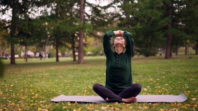 Bastante-joven-mujer-es-terminando-la-práctica-de-yoga-sentado-en-la-estera-de-los-ojos-y-respirar-tranquilo-día-de-otoño-en-el-parque-Actividad-recreativa-y-el-concepto-de-zonas-urbanas-