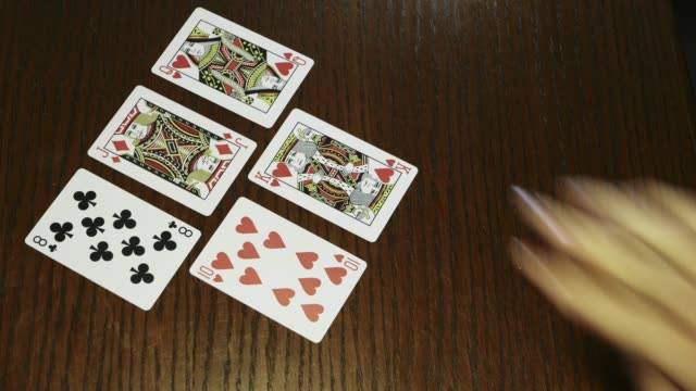 hands-holding-shuffle-playing-card-deck-on-wooden-table