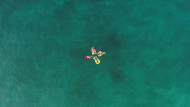 Aerial-view-of-group-holding-hands-on-inflatable-mattress-on-Atokos-island-