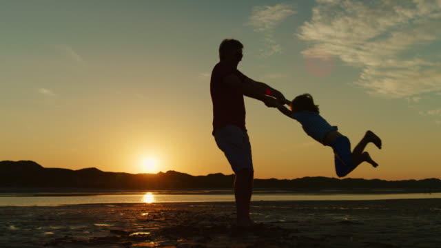 Silhouette-Of-Father-And-Son-Playing-Together-At-The-Beach-