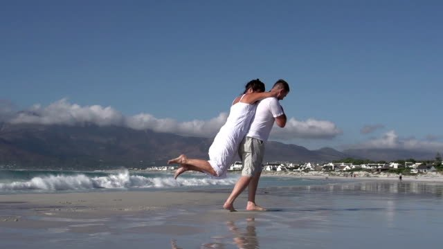 Slow-motion-of-romantic-couple-spinning-around-on-the-beach-Cape-Town-South-Africa