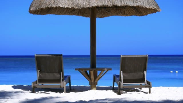 4K-Perfect-holidays-view-:-2-deckchairs-and-an-umbrella-with-ocean-view