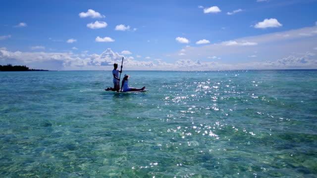 v03860-vuelo-drone-vista-aérea-de-Maldivas-playa-2-personas-pareja-hombre-mujer-relajante-en-paddleboard-en-isla-paraíso-soleado-con-cielo-azul-aqua-agua-mar-4k
