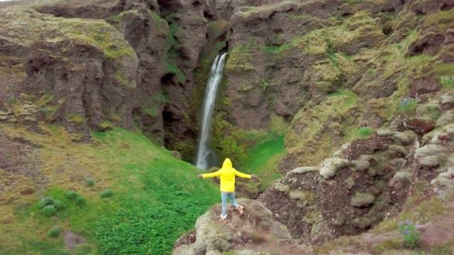 Vista-aérea-Drone-de-joven-brazos-extendidos-en-espectacular-cascada-en-Islandia--4-K-video