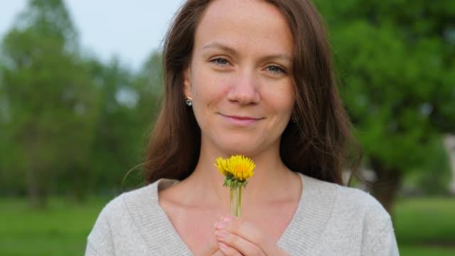 Mujer-de-sostener-en-las-manos-flores-de-diente-de-León