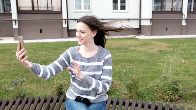 Hermosa-mujer-despide-por-el-vídeo-agitando-y-envía-un-beso-llamando-en-el-teléfono-móvil-