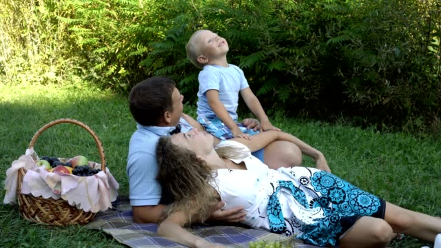 Family-picnic-in-nature-Mom-dad-and-son-lie-on-the-grass-in-the-Park-near-the-fruit-basket-They-look-up-laugh-play-and-have-fun-Boy-eating-grapes-