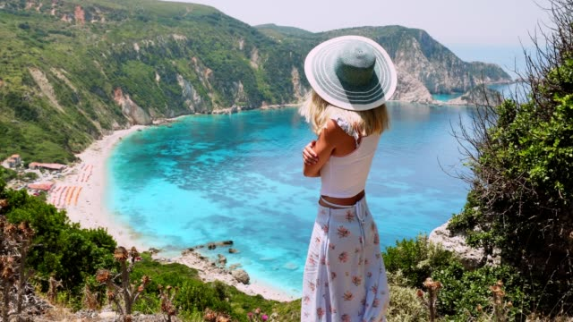 Cute-woman-in-hat-admiring-landscape-on-greek-island-Blonde-posing-in-front-of-amazing-scenery-of-Petani-bay-Summer-vacation-lifestyle-travel-adventure-carefree-joy-and-happiness-concept-4k-video