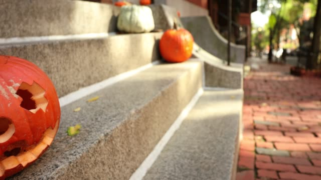 A-scary-carved-pumpkin-Jack-o-Lantern-on-the-steps-of-a-home-before-Halloween-trick-or-treat