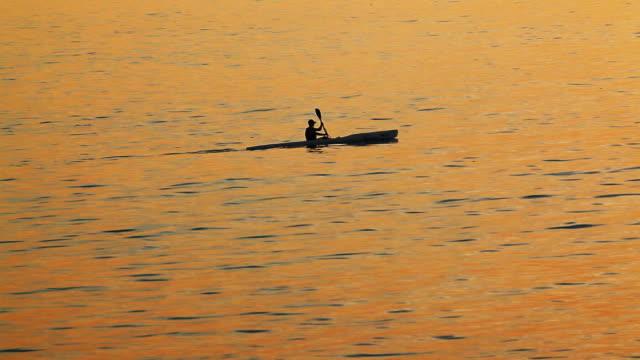 Man-paddling-a-kayak-in-the-sunset