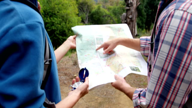 Vista-posterior-de-excursionistas-que-quieren-un-mapa-con-una-brújula