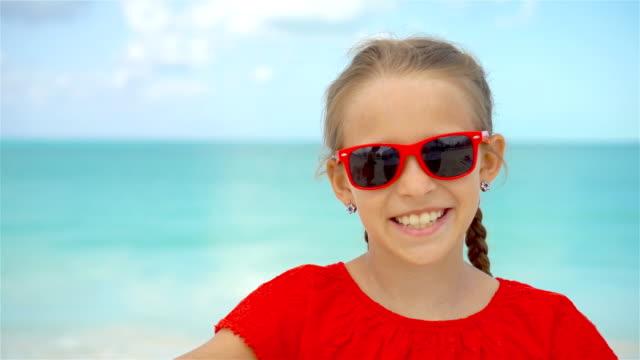 Kleines-Mädchen-unter-Selfie-Porträt-mit-ihrem-Smartphone-am-Strand