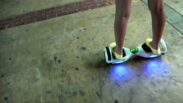 Girl-using-hoverboard-a-self-balancing-two-wheeled-board-The-gyroscope-based-dual-wheel-electric-scooter-is-also-called-a-smart-balance-wheel-