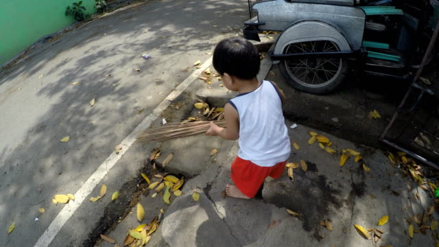 Two-year-old-boy-baby-sweeping-the-street-with-broomstick