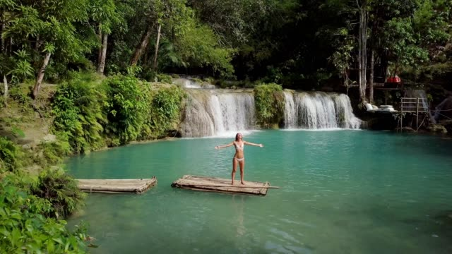 Drone-shot-joven-en-balsa-de-bambú-que-naturaleza-en-cascada-en-la-selva-brazos-amplia-abren-gente-viaje-vacaciones-concepto-Resolución-de-4K-Filipinas