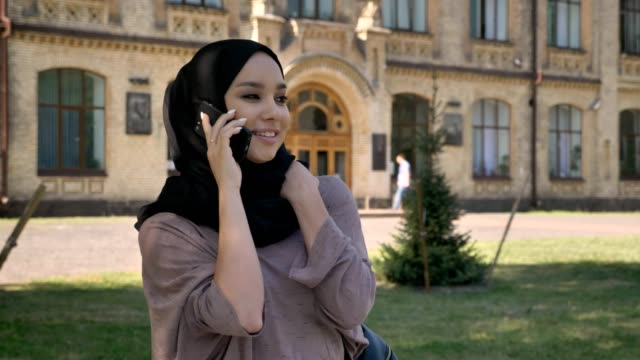 Young-sweet-muslim-girl-in-hijab-is-talking-on-phone-and-laughing-in-daytime-in-summer-building-on-background-religiuos-concept-communication-concept
