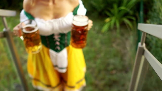 Sexy-Oktoberfest-waitress-carries-two-large-glasses-of-beer-The-girl-walks-barefoot-on-the-grass-and-climbs-the-stairs-Bavarian-traditional-costume-erotic-neckline