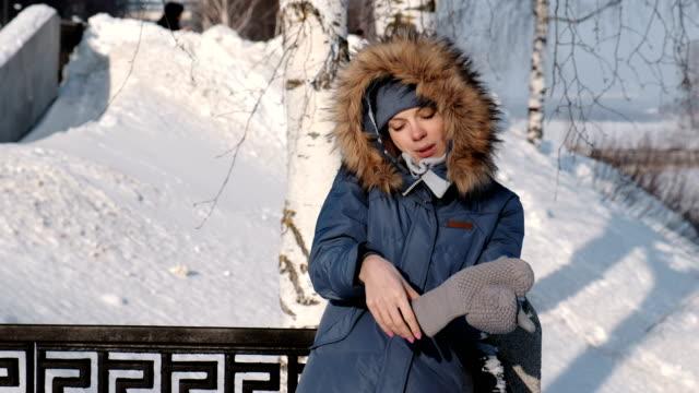 Mujer-en-azul-abajo-de-la-chaqueta-con-capucha-de-piel-llamando-a-su-teléfono-celular-en-el-parque-de-invierno-y-poner-en-su-guante-