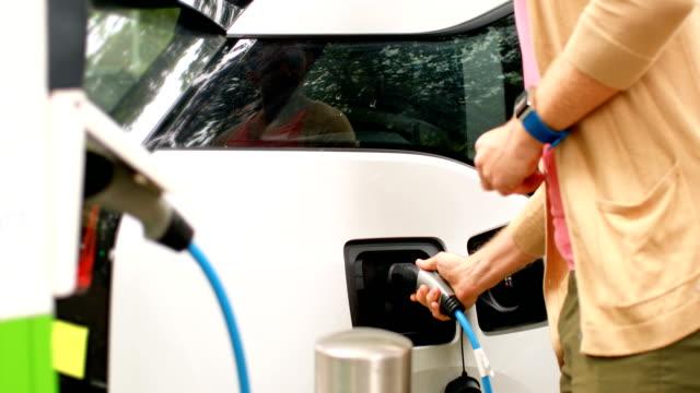 Hombre-carga-un-coche-eléctrico-en-estación-4k-de-carga
