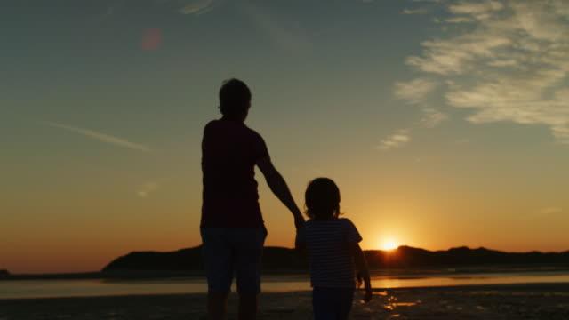 Silueta-del-padre-y-el-hijo-caminando-juntos-en-la-playa