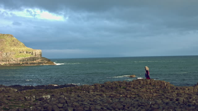 4k-Fantasy-Shot-on-Giant-s-Causeway-of-a-Queen-Standing-in-Wind