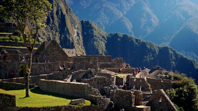 Gente-camina-alrededor-de-antiguas-ruinas-en-las-montañas