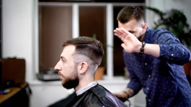 Joven-peluquero-permanente-y-elegante-corte-de-pelo-de-hombre-atractivo-con-clipper-en-peluquería-Hombre-con-barba-sentado-en-la-silla-con-negra-capa-protectora-contra-el-espejo-y-mirando-a-sí-mismo