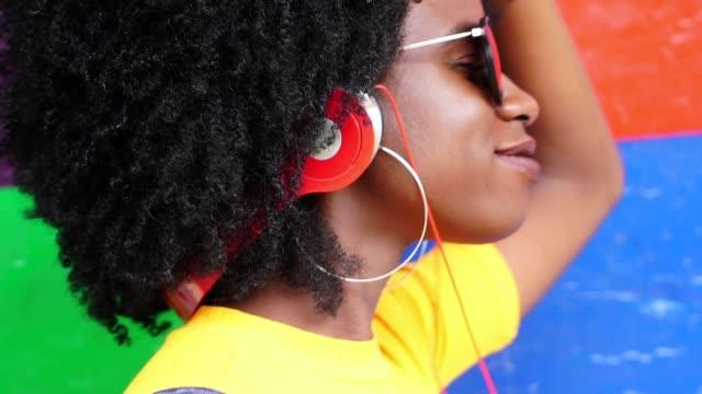 Escuchar-música-de-chica-guapa-con-sus-auriculares-con-colores-de-fondo