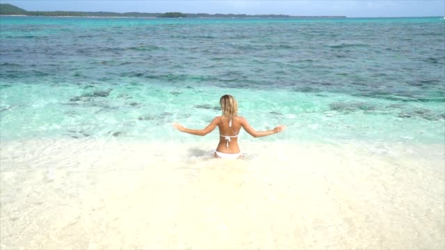 Mujer-joven-relajándose-en-una-playa-tropical-jugar-y-salpicar-con-agua