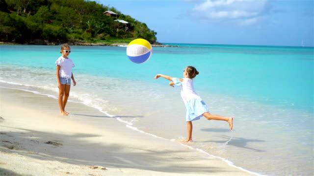 Poco-encantadores-niñas-jugando-con-pelota-en-la-playa
