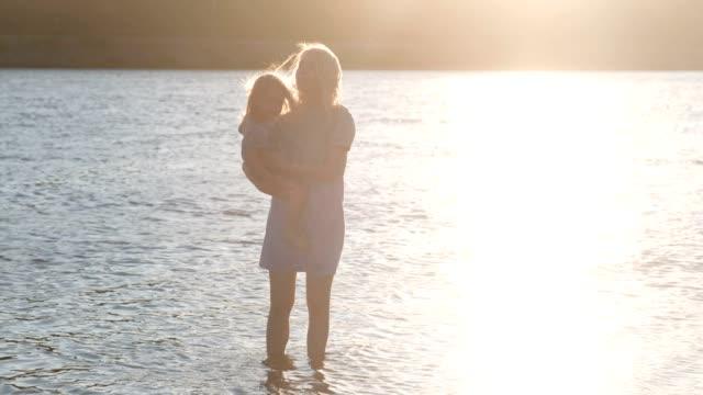 Hermosa-rubia-madre-e-hija-caminando-junto-al-río-en-el-agua-al-atardecer.